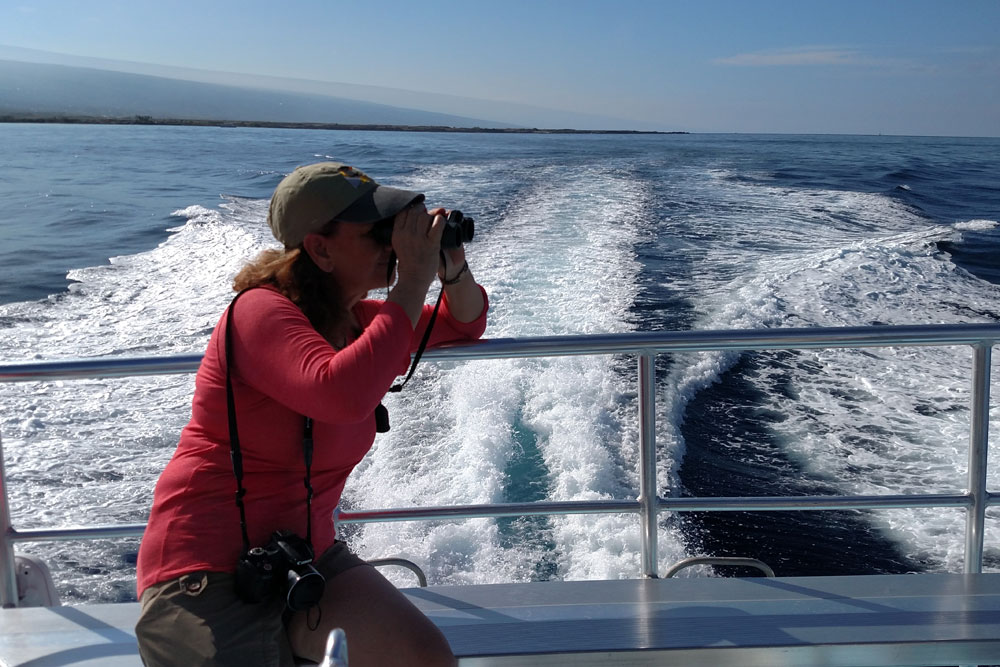 woman on boat looks through binoculars